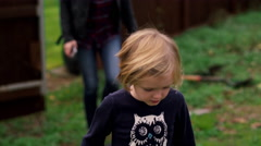 A little girl and her mother walking in their back yard Stock Footage