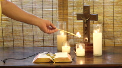 Man lights candle in home Christian altar place of worship. Stock Footage