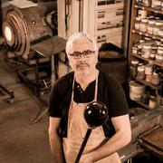 Glassblower forming molten glass in his worshop Stock Photos