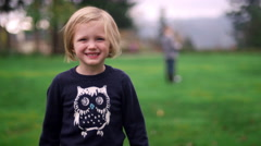 A little girl smiling at the camera at a park, and then saying peek-a-boo Stock Footage