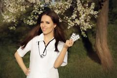 Spring Woman Doctor Smiling and Holding Pills - stock photo