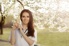 Spring Woman Doctor Smiling and Holding Respiratory Spray - stock photo