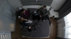 Woman offended at her boyfriend gathers clothes, swearing. top view Stock Footage