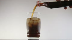 Pouring fresh coke from the bottle with ice cubes isolated on white background. Stock Footage