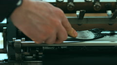Caucasian male putting ink on a vintage letterpress machine roll Stock Footage