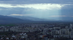 Sun rays penetrate through clouds and illuminate the valley with the city and Stock Footage