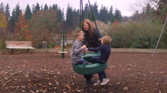 A mother pushes her two kids on a tire swing at the playground Stock Footage