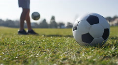 Footballer doing kicks ups in the background as a soccer ball is in the foregrou Stock Footage