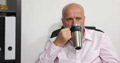 Stock Video Footage of Pan View Thoughtful Manager Drinking Coffee Thinking Serious Company Business