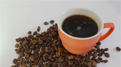 Hot, black coffee in cup and caffee beans on white background Stock Footage