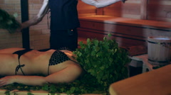 Slap on the woman with a brooms in a sauna Stock Footage