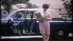 Off duty cop at home with 1963 Plymouth police car -2708 vintage film home movie Stock Footage
