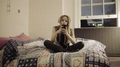 Teenage girl in bedroom on smart phone with headphones Stock Footage