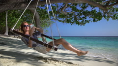 A young woman uses a smartphone and enjoys relaxing on the tropical beach. Stock Footage