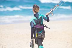 Female kiteboarder with kiteboarding equipment. Stock Photos