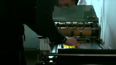 Caucasian male preparing stamp for a letterpress print Stock Footage