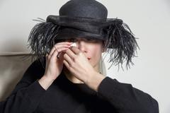 Portrait of a woman with black dress and hat looking sad Stock Photos