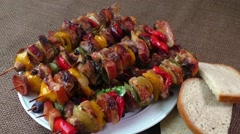 Grilled meat skewers with vegetables on a white plate Stock Footage
