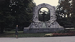 Vienna 1966: woman visiting Johann Strauß statue at Stadtpark Stock Footage