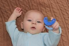 Baby boy holding a blue nipple - stock photo