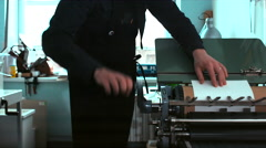 Making a print on a vintage letterpress machine. Tracking dolly out shot Stock Footage