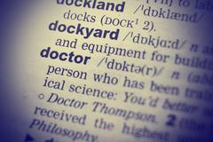 Close-up of word in English dictionary. Doctor definition and transcription Stock Photos