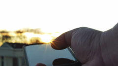 Man Using Smartphone at Sunset with Sun Flares, 4K Stock Footage