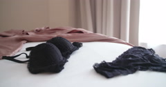 Close up of woman picking her underwear up on bed - stock footage