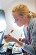 Woman eating meal on airplane. Stock Photos