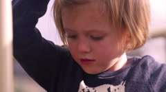 A little girl climbing across a play structure, close up, slow motion Stock Footage