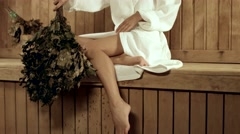 Woman in bathrobe sitting in the sauna Stock Footage