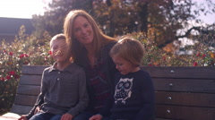 A mother and two kids posing for a picture on a bench at the park Stock Footage