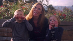 A mother and two kids sitting on a bench at the park and making funny faces Stock Footage