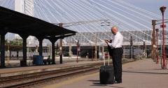 Stock Video Footage of Railway Station Businessman Wait Train Travel Mobile Talking Financial Affairs