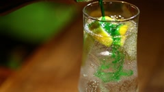Stock Video Footage of Slice of lemon in a glass of soda, with ice cubes and syrup.