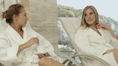 Two girl friends relaxing in a spa center, chatting over a cup of tea Stock Footage