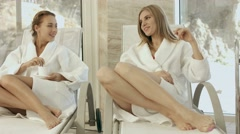 Two girl friends relaxing in a spa center, chatting over a cup of tea - stock footage