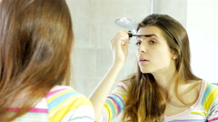 Beautiful young woman putting mascara and makeup in front of mirror in bathro Stock Footage