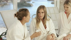 Stock Video Footage of Three young women in a bathrobe laughing and gossiping