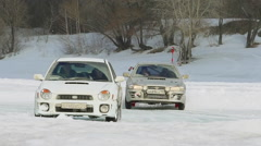 SLOW: A Two Racing Cars Drift On A Ice Road In A Race - stock footage