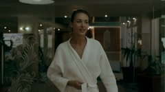 Young woman takes off bathrobe on the way to the indoor pool Stock Footage