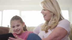 4K Grandmother & young granddaughter looking at computer tablet together at home Stock Footage