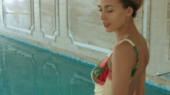 Young slender woman in a bathing suit  douse in the indoor pool in the spa - stock footage