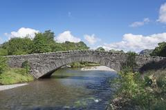 Old stone bridge in Rosthwaite Lake District Cumbria England United Kingdom - stock photo