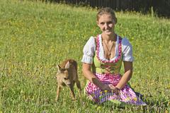 Woman in dirndl with a tame fawn in a flower meadow Tyrol Austria Europe Stock Photos