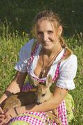 Woman in dirndl with a tame fawn sitting in her lap in a flower meadow Tyrol Stock Photos
