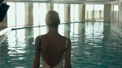 Beautiful woman swimming in the indoor pool Stock Footage