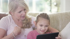 4K Grandmother & young granddaughter making video call on computer tablet Stock Footage