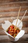 Noodles with pork and vegetables in take-out box on wooden table - stock photo
