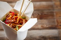 Noodles with pork and vegetables in take-out box on wooden table Stock Photos
